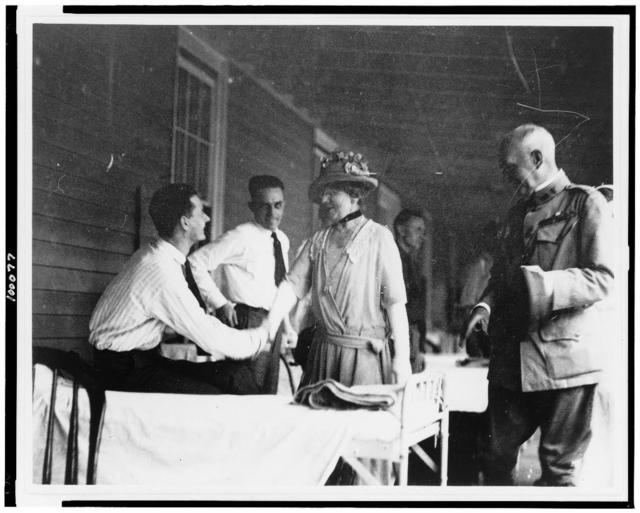 [Mrs. Warren G. Harding shaking hands with man seated on bed in military barracks(?)]