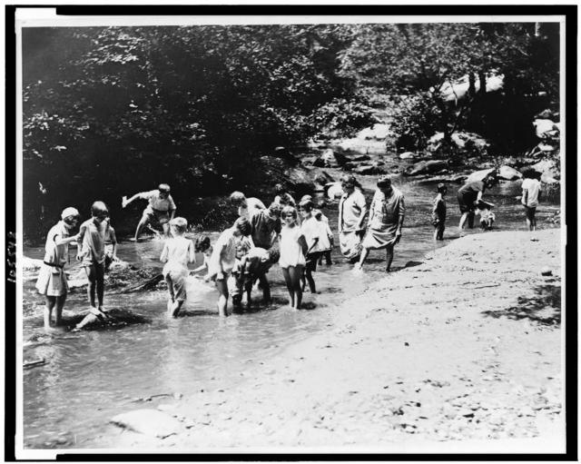 On one of the hottest days recorded in the National Capital both women and children rush to the water for relief. Snapped in Rock Creek Park