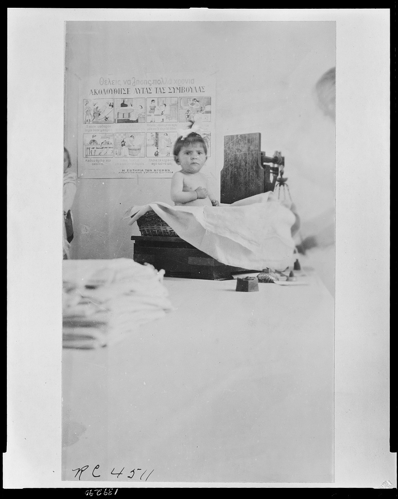 One of the Greek babies on the scale at the Athens infant welfare clinic operated by the [erased].  American nurses are helping to care for many of the Greek babies in the Hellenic capital where they have been suffering from lack of care and attention