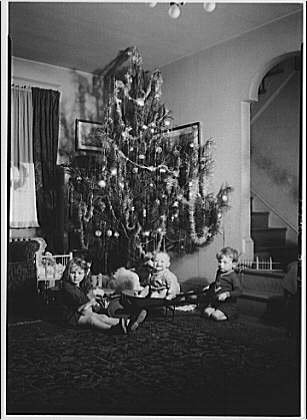 Portrait photographs. Children with tricycle and wagon next to Christmas tree V