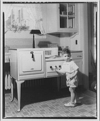 Potomac Electric Power Co. electric appliances. Boy in front of stove