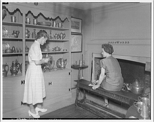 Questers antique shop. Two ladies with silver display