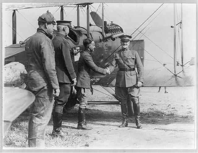 Reception of the Alaskan flyers at Washington, D.C. - Gen. Pershing congratulating Capt. Street of the squadron [alongside airplane, as 2 other men watch]