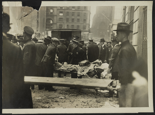 Removing bodies after Wall St. explosion Volunteers removing the bodies of the dead following the explosion in Wall Street yesterday. Photo taken in front of the U.S. Assay Office / / Underwood & Underwood.