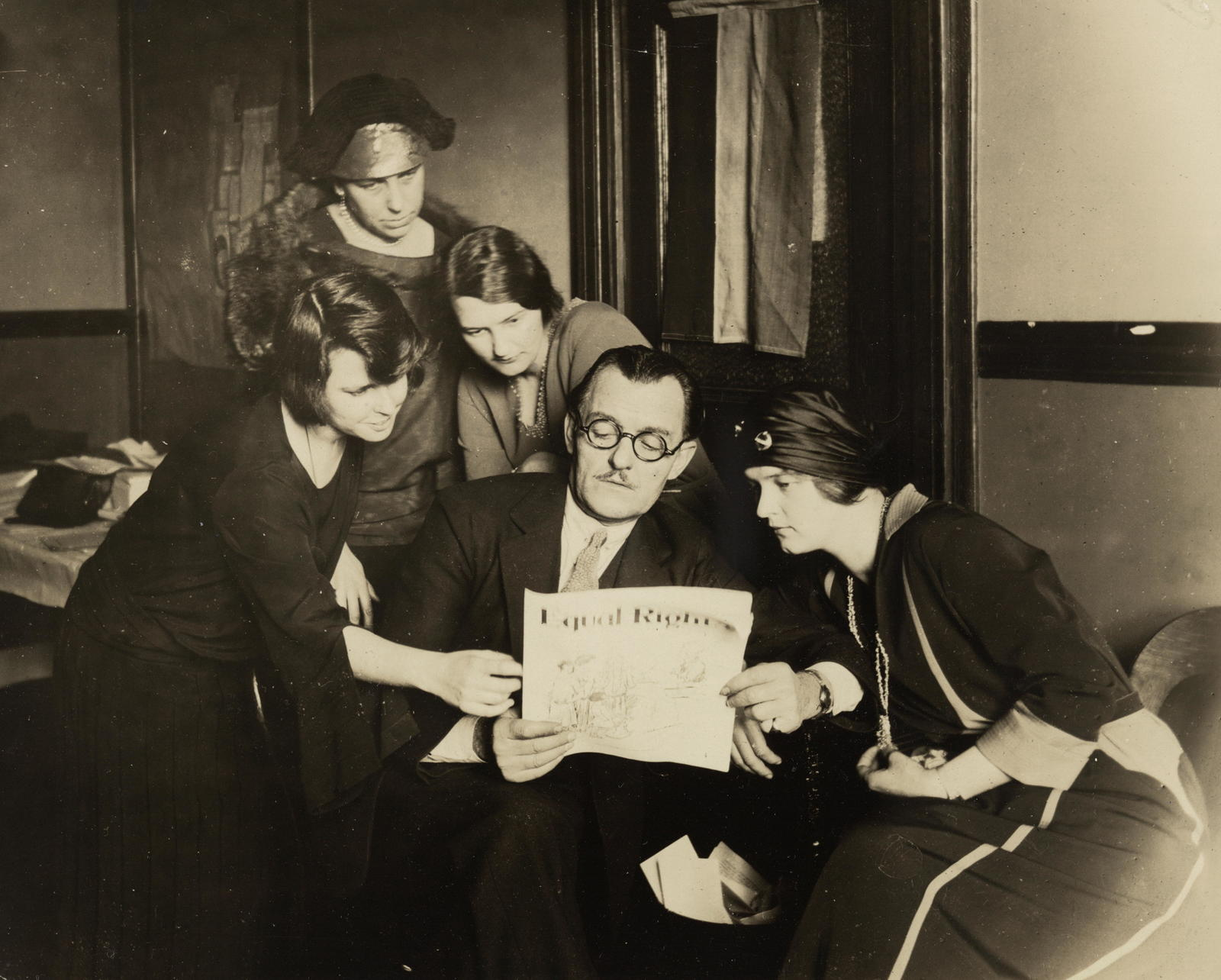 "Richard Bennett, noted actor, calling at National Woman's Party Headquarters, underwrites the Equal Rights campaign, and declares: - ""Certainly I am a feminist and will stand back of you women until the Equal Rights Amendment is passed by Congress."" Mr. Bennett is surrounded by a group of National Woman's Party leaders. (Left to right) Anita Pollitzer, National Secretary of the Woman's Party, Richard Bennett, Wilma Henderson, National Organizer: (upper left) Mrs. Everett Bray, a Founder, and Jessica D. Henerson, member of the Massachusetts State Committee."