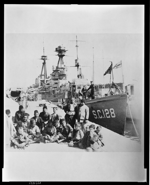 "Six American sub-chasers in the Greek Islands were at the disposal of American Red Cross workers in Salonica This cooperation between the American Navy and Red Cross facilitated relief work among the destitute island folk. On the wharf, beside ""sub-chaser 128"" are some Greek boys and men who have been brought into Salonika [sic] to the Red Cross hospital. The British battleship can be seen in the back-ground."