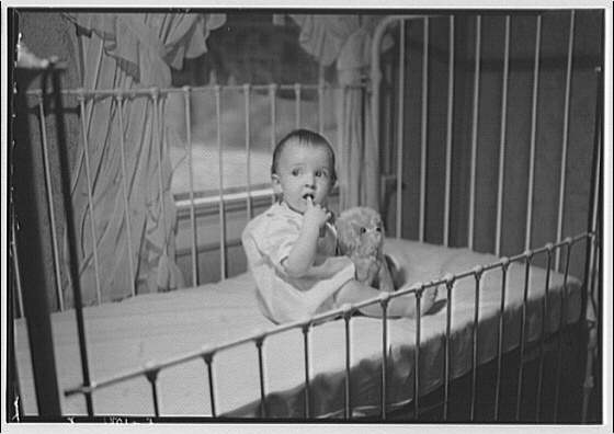 Thomas J. Meaney family and children. Meaney baby in crib with stuffed animal