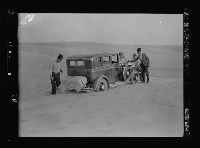 To Sinai by car. Car stuck in the midst of a sand dune. Sand drifts across the road
