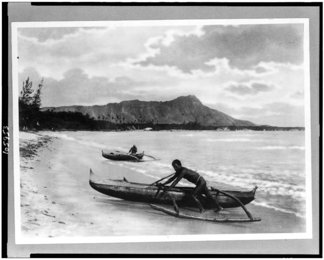 [Two natives with outrigger canoes at shoreline, Honolulu, Hawaii]