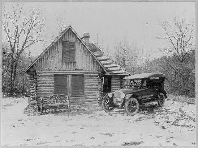[Two women in new Oldsmobile in front of log cabin, Rock Creek Park, Washington, D.C.; picture made for Oldsmobile Sales Co.]