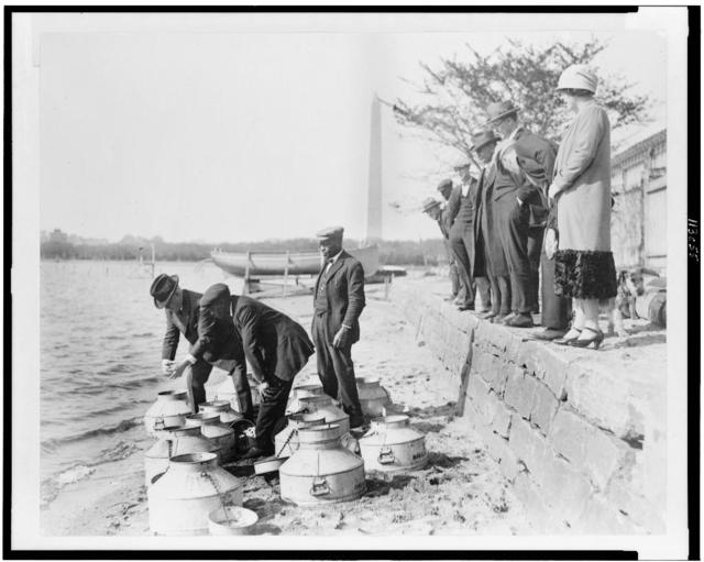 [U.S. Fish Commissioner, Henry O'Malley, stocking fish in the Potomac River, at the Tidal Basin, Washington, D.C., with the Washington Monument in the background]