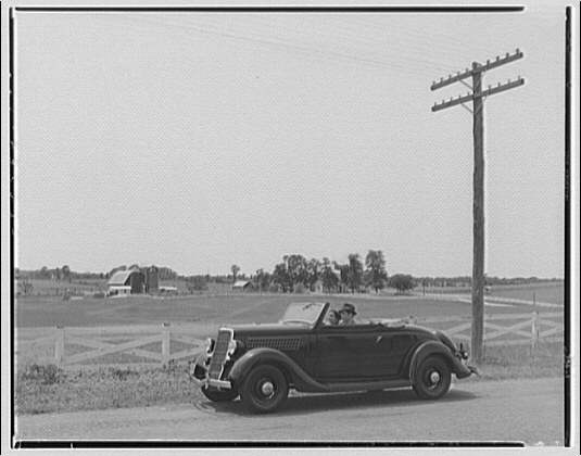 Vaughan Connelly. Side view of car and farm in background