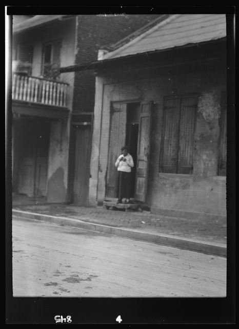 View from across street of a woman standing in a doorway in the French Quarter, New Orleans