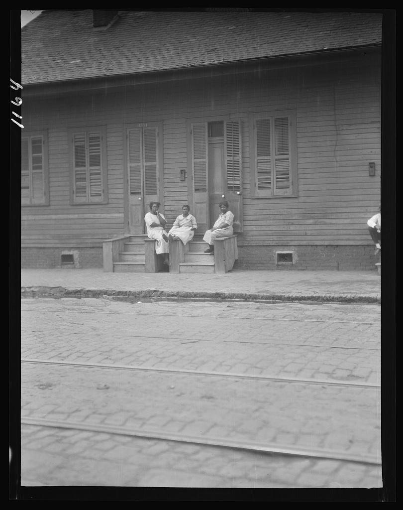 View from across street of three women talking, New Orleans or Charleston, South Carolina