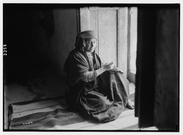 Wady Shaib Es-Salt, Amman, etc. Christian Bedouin girl of Es-Salt, sitting in doorway, sewing.