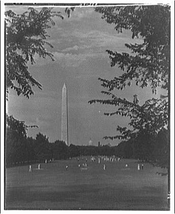 Washington Monument. View of Washington Monument from parkway with people playing I