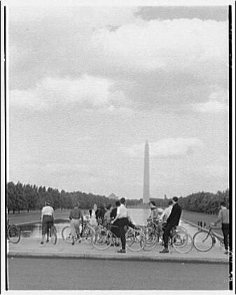 Washington Monument. View of Washington Monument from reflecting pool with people and bicycles