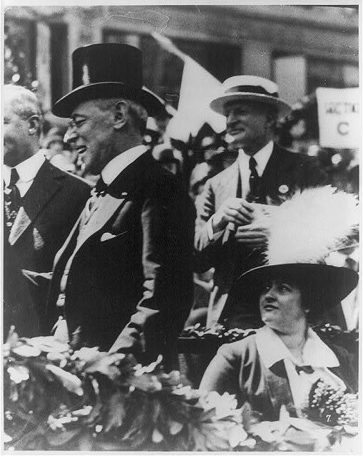 [Woodrow Wilson, in a top hat, standing while his wife Edith Bolling Galt looks on]