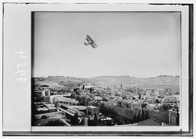 Airplane over Jerusalem & military force at Damascus Gate, seen from roof of Notre Dame building