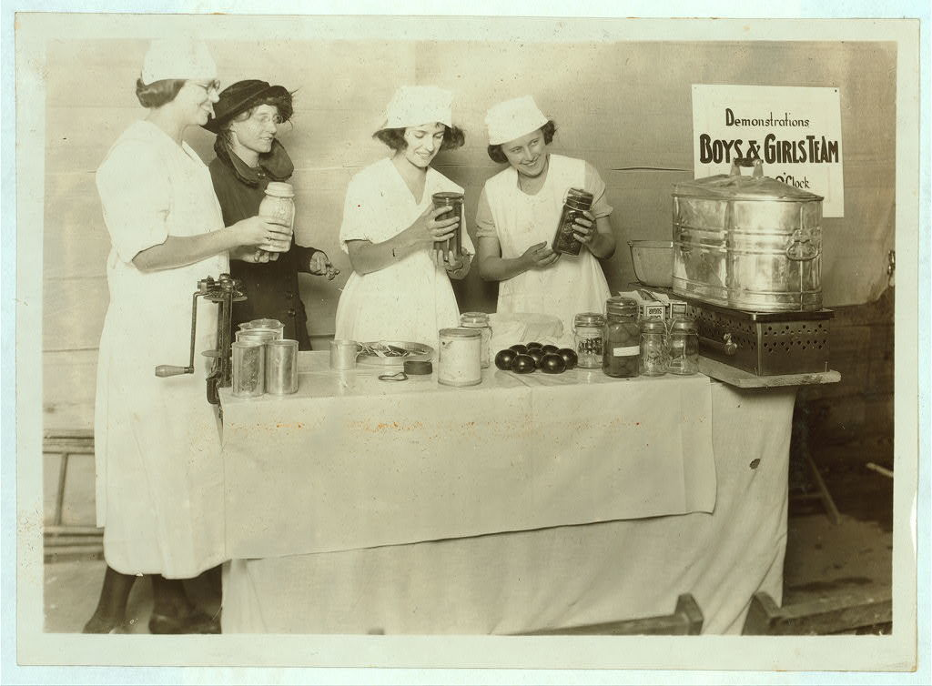 "A ""Demonstration team"" composed of three prize-winning Cabell Co. girls. They are showing the visitors at the Fair how team work makes for efficiency in canning their farm products. State 4 H Fair. (See Photos No. 48, 49.)  Location: Charleston, West Virginia / Photo by Lewis W. Hine."