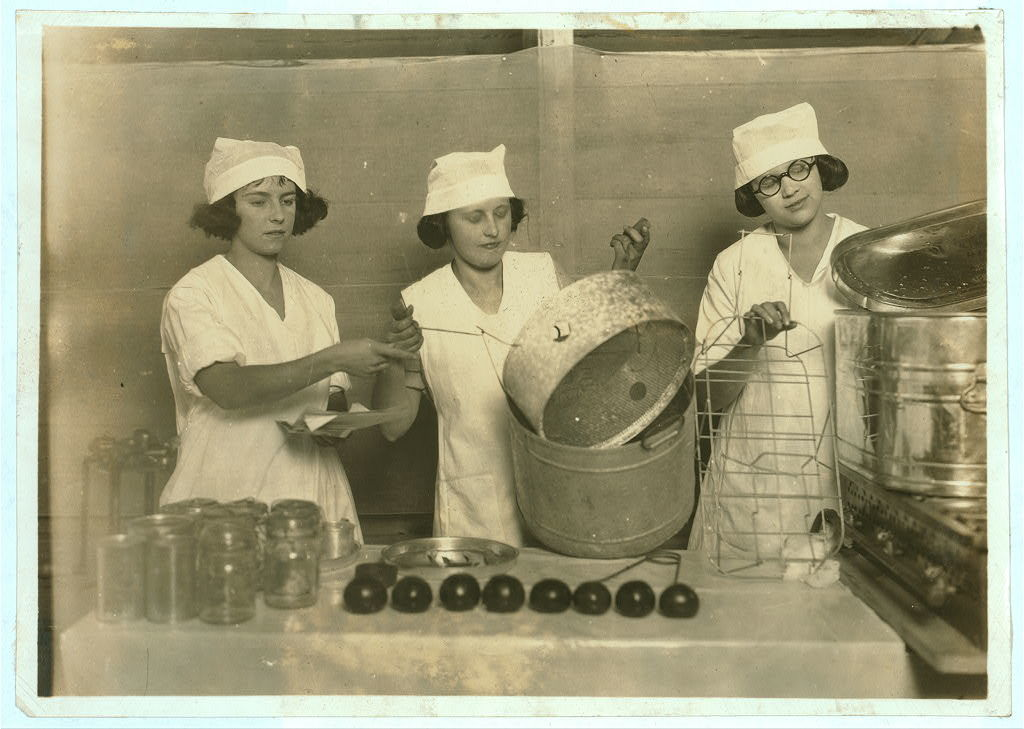 """A """"Demonstration team"""" composed of three prize-winning Cabell County girls. They are showing the visitors at the Fair how team work makes for efficiency in canning their farm products. State 4 H. Fair, Charleston, W. Va.  Location: Charleston, West Virginia / Photo by Lewis W. Hine."""