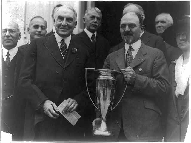 As Honorary Vice President of the National Tuberculosis Assn., President Harding presented to Dr. Frank Ballou, Supt. of Schools, the cup offered for the schools having the largest enrollment based on population