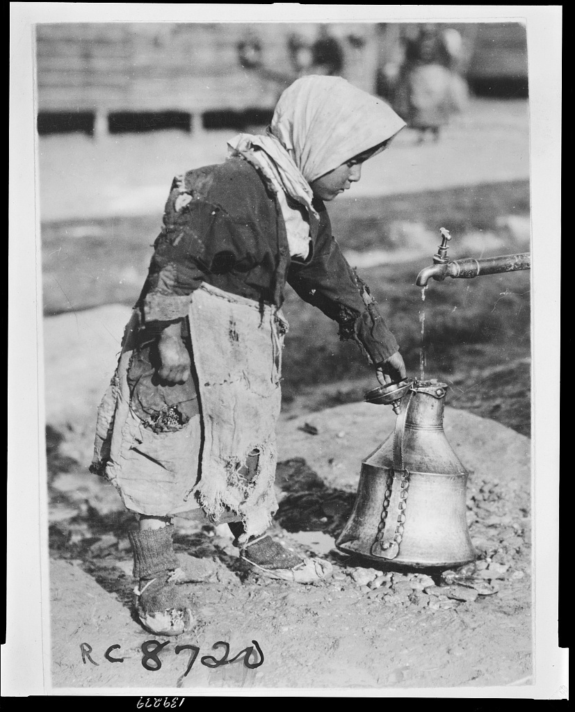 At the well A young ragged member of the colony of Greeks who have reached Salonica from the Caucasus for the purpose of settling again in their native land. The water supply at the camp was installed by the British army during the war.
