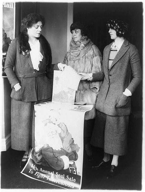 Ethel Barrymore acts as saleslady at the Christmas Seal booth in Washington, D.C. With Miss Barrymore are Miss Carlia(?) Campbell and Mrs. Sidney Thomas, leaders in last years sales campaign