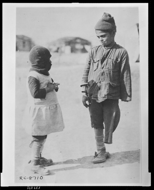 Exchanging news - two of the smaller members of the Greek colony which has been set up for repatriates from the Caucasus outside Salonica The boy lost one of his arms and legs in a railway accident. He is a great favorite in the camp.