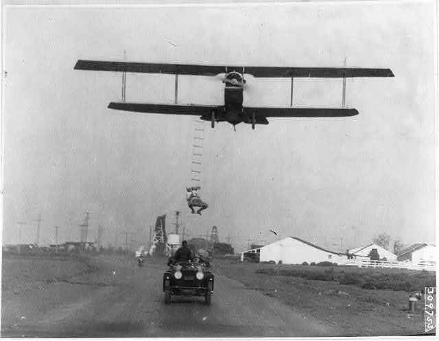 "[""Fearless Freddie"", a Hollywood stunt man, clinging to a rope ladder slung from a plane flown by A.M. Maltrup, about to drop into automobile below: automobile shown]"