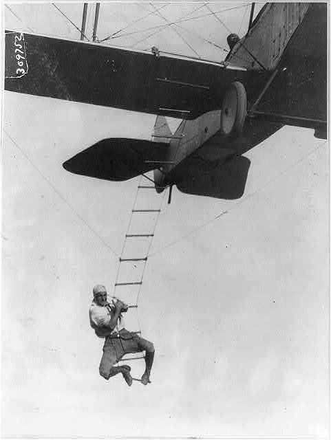 "[""Fearless Freddie"", a Hollywood stunt man, clinging to a rope ladder slung from a plane flown by A.M. Maltrup, about to drop into automobile below: automobile not shown]"