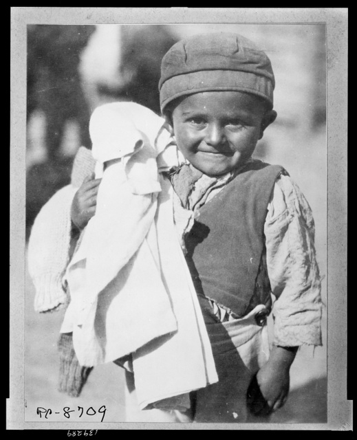 Fresh clean clothing - is welcomed by this youngster jud[g]ing by his expression He is one of the young members of the camp of Greeks from the Caucasus brought back to colonize the rewon province of Thrace and temporarily stranded in Salinica [i.e. Salonica] where the American Red Cross is helping them.