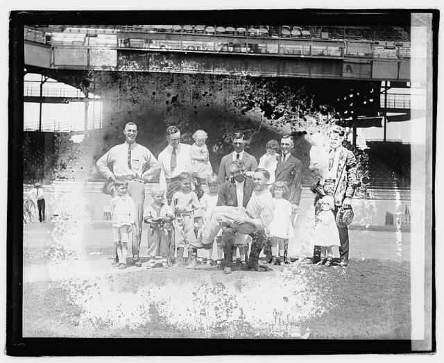 [Group portrait of men and children in stadium]