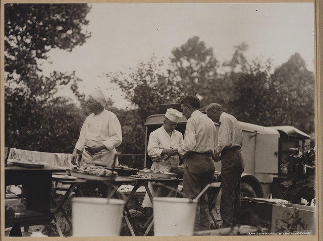 [Henry Ford and Harvey Firestone assisting two chefs by peeling potatos at a Ford-Edison camping trip]