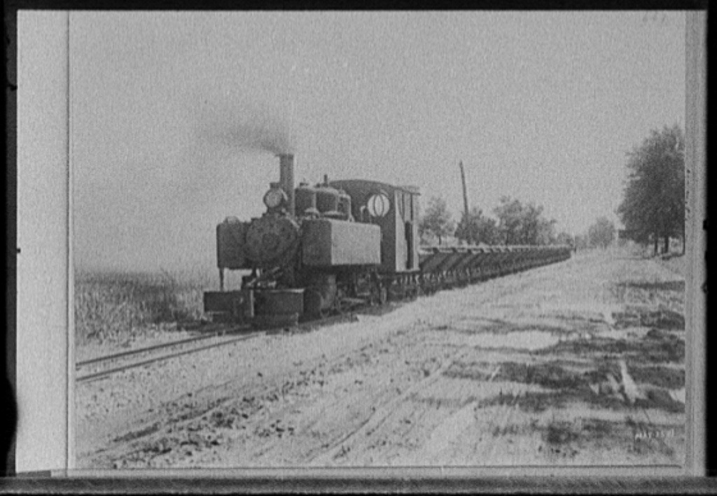 [Locomotive pulling cars alongside road, possibly road construction in Michigan]