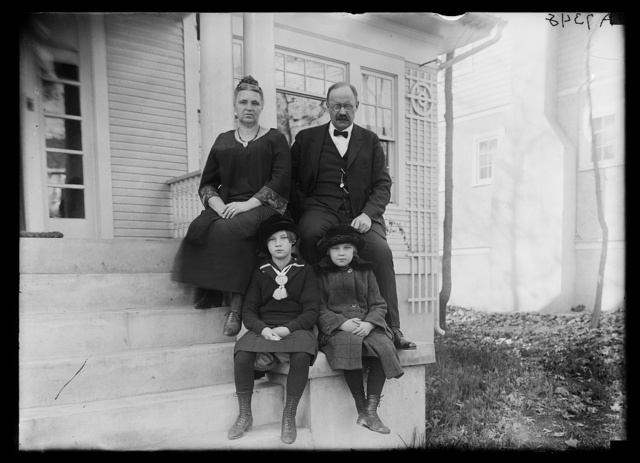 [Magnus Johnson with family? on front porch of house]