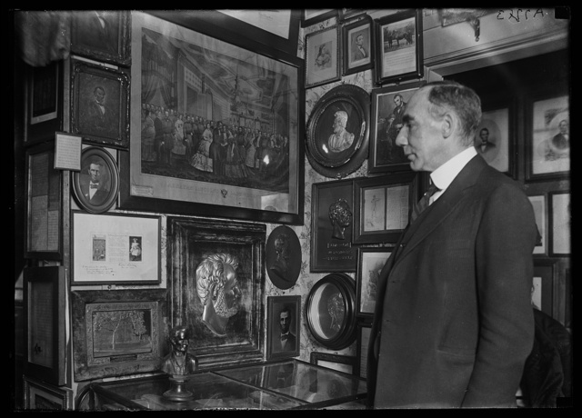 [Man looking at collection of Lincoln pictures]
