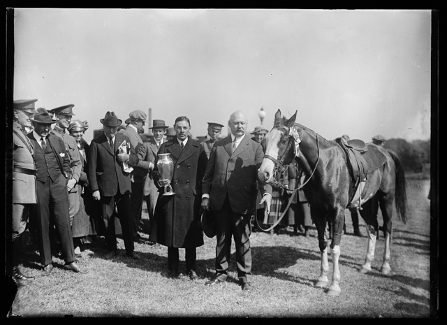 [Man with Trophy and John W. Weeks next to horse]