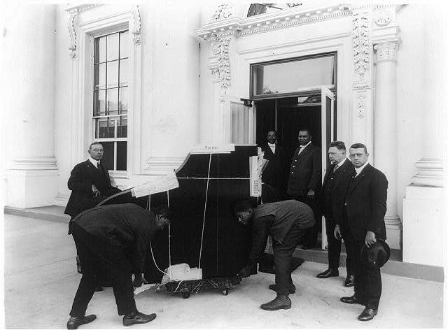 [Men moving a piano, into the White House(?), in Washington, D.C., 1921(?)]