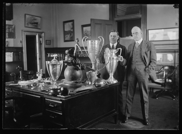 [Men with trophy cups on desk]