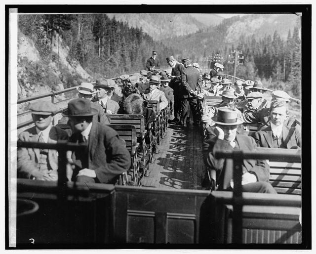 [Passengers on roof deck of train traveling through mountains]