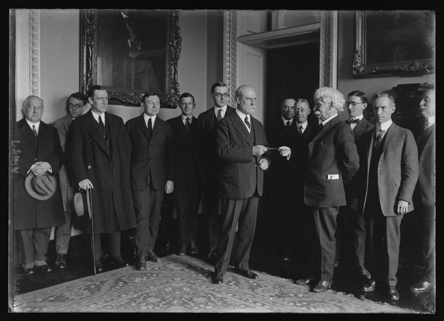 Secy. Hughes being presented with a pair of gold shears on behalf of the newspapermen covering the State Dept.