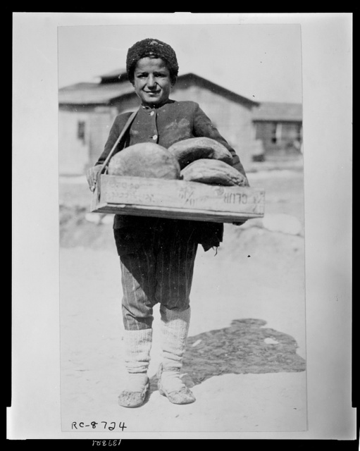 The bread boy - at the camp at Salonica for Greeks who have been brought back from the Caucasus for the purpose of colonizing their country's rewon province of Thrace They have been delayed at Salonica where they landed and their plight has become so bad that the American Red Cross and other relief agencies have stepped in to stem the misery and death.