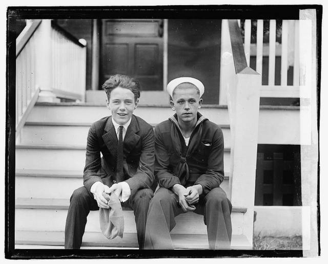 [Unidentified young man and sailor seated on porch steps]