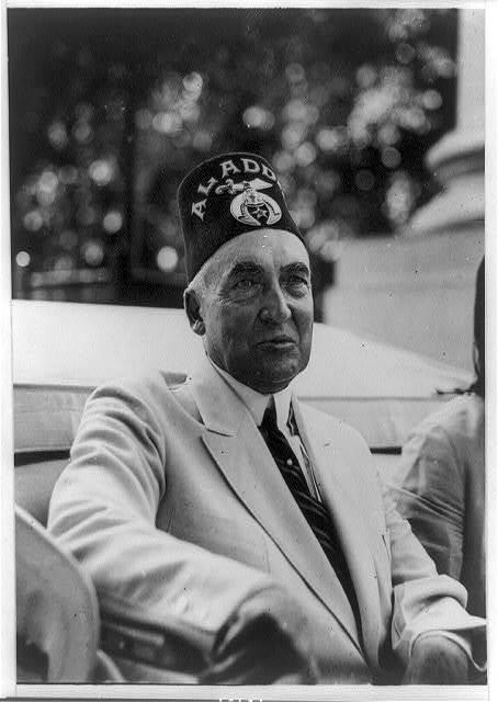 [Warren G. Harding, half-length portrait, seated in vehicle, facing right, wearing mason's hat]