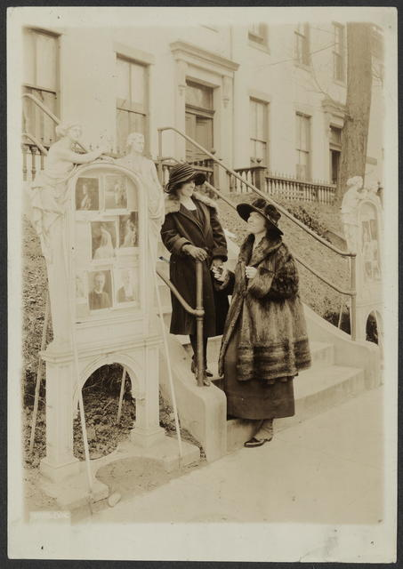 A breathing spell between campaigns - Miss Anita Pollitzer (left) and Miss Elsie Hill, secretary and chairman, respectively of the Woman's Party, meet on the steps of the Party headquarters.  The Bulletin Board in the picture saw the stormiest days of the suffrage campaign and still tells of the Party's activities on behalf of women.