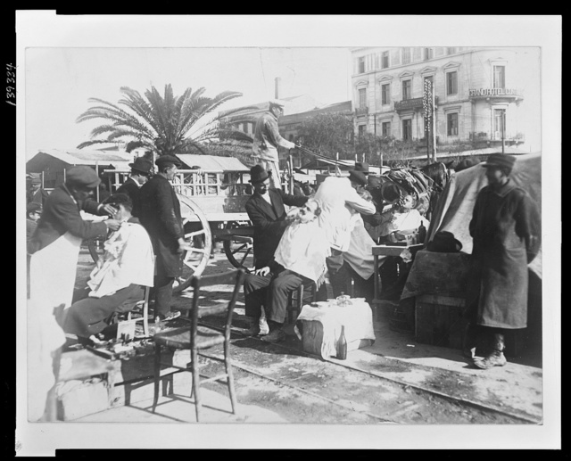 "A section of ""barber's row"" Enterprising refugees among the hundreds of thousands of Greeks and Armenians who fled from Asia Minor to Greece have set up stools, boxes, chairs and everything that can be sat on in a long row on the quay in Piraeus, the seaport of Athens, and shave and cut the hair of customers."
