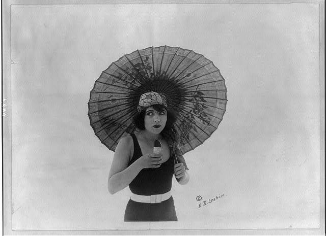[Betty Compson, half length portrait, standing, with umbrella, in bathing suit, facing slightly right, eating Eskimo Pie. Movie star]