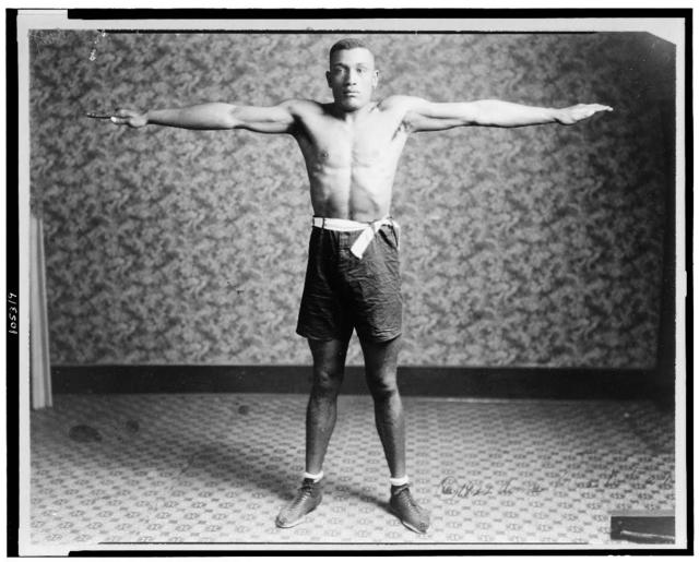 [Boxer Tut Jackson clothed in boxing trunks, full-length portrait, standing, facing front, with his arms extended out from his sides, showing his reach]