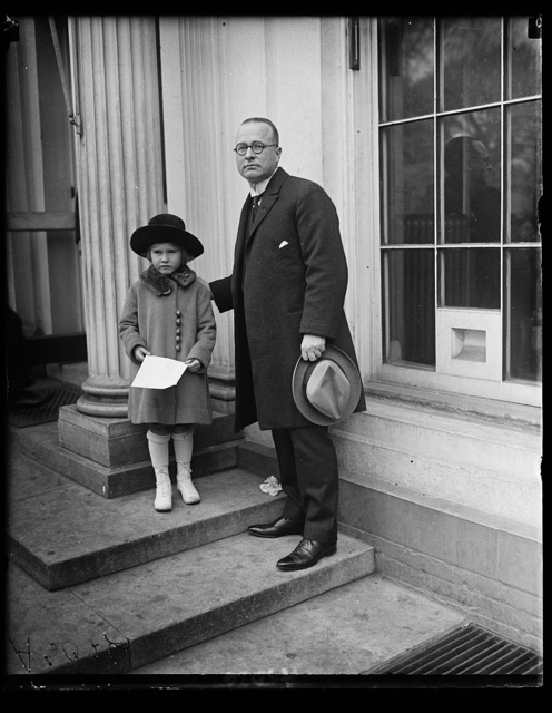 Frances Glover and her father third [...] P.M.G. Glover. Miss Glover presented Pres. Harding with the first of three new [...] one portraying the Arlington amphitheater